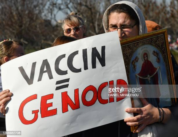 A woman holds a placard reading Vaccin = Genocide and a ChristianOrthodox icon during a demonstration against a draft law to be adopted by the...
