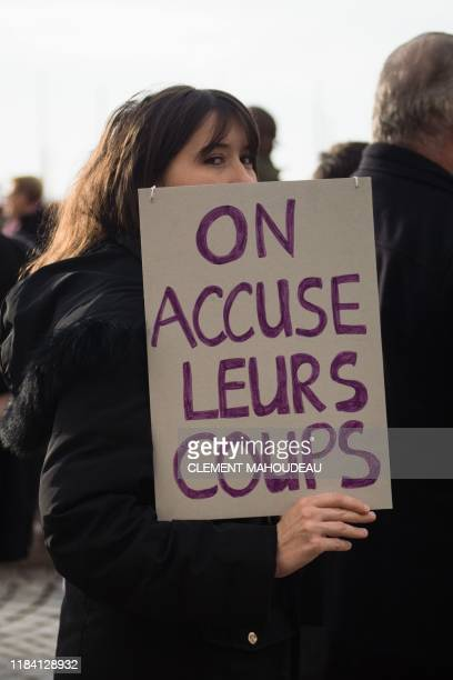 A woman holds a placard reading We take their blows during a protest march to condemn violence against women on November 23 2019 in Marseille...