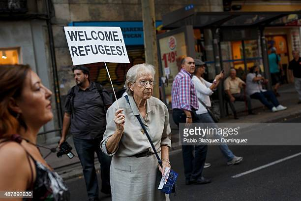 A woman holds a placard reading 'Welcome refugees' as she takes part in a demonstration to show solidarity and support for refugees on September 12...