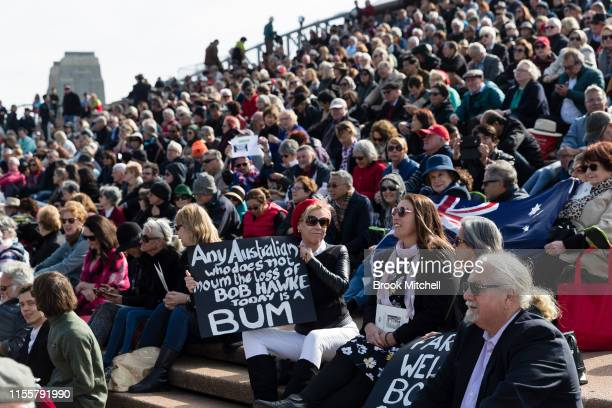 A woman holds a placard repeating one of Bob Hawkes famous quotes at the Sydney Opera House on June 14 2019 in Sydney Australia Robert James Lee...