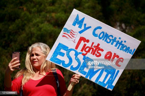 Woman holds a placard saying her constitutional rights are essential. Protesters gather outside Indiana Governor Eric Holcomb's mansion in the 4700...