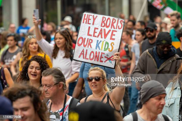 Woman holds a placard saying Hey Boris leave our kids alone while protesting against the covid-19 vaccine being available to children in the near...