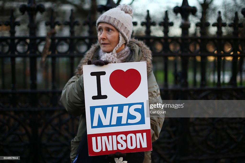 A woman holds a placard saying 'I heart NHS' as she takes part in a picket outside St Thomas' Hospital on January 12, 2016 in London, United Kingdom. Junior doctors in England have gone on strike in a dispute with the government over a new contract. The doctors are only providing emergency cover during the 24-hour walkout, which started at 8:00am with the NHS so far postponing 4,000 routine treatments.