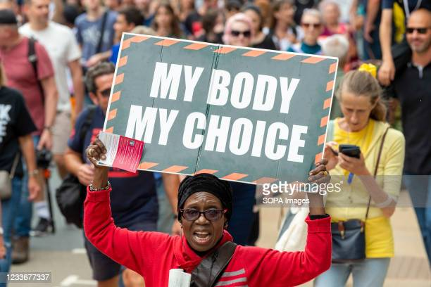 Woman holds a placard saying My body my choice during the Freedom March demanding an end to COVID-19 restrictions, London.