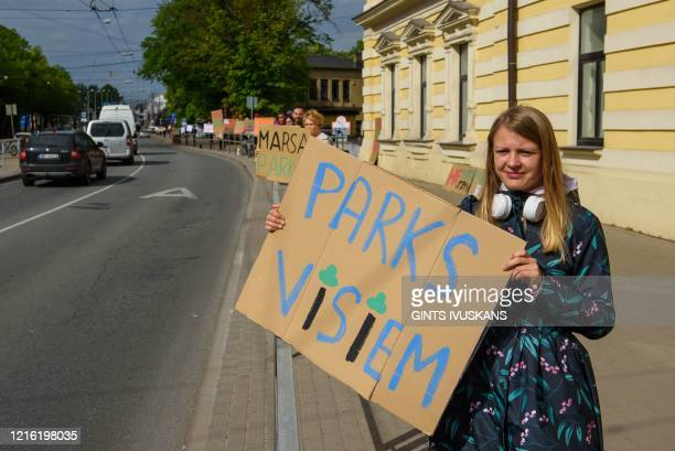 A woman holds a placard which reads Park for everyone during a protest to save trees in Riga Latvia on May 28 2020 Around 400 protesters made a...
