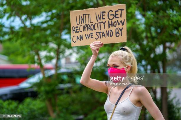 A woman holds a placard while protesting near the area where a Minneapolis Police Department officer allegedly killed George Floyd on May 26 2020 in...