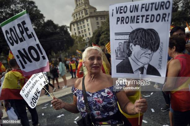 A woman holds a placard with a caricature of Catalan president Carles Puigdemont during a demonstration called by Catalan Civil Society under the...