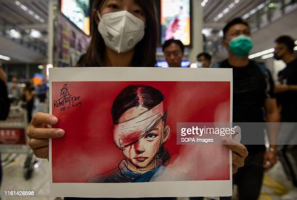 A woman holds a placard with a drawing depicting an injured protester during a sitin protest at the Hong Kong International Airport In response to...