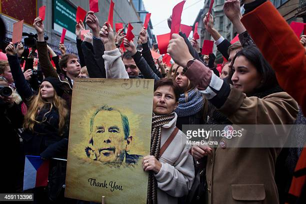 A woman holds a placard with a picture of former President of Czechoslovakia and Czech Republic Vaclav Havel as people show red card as they protest...