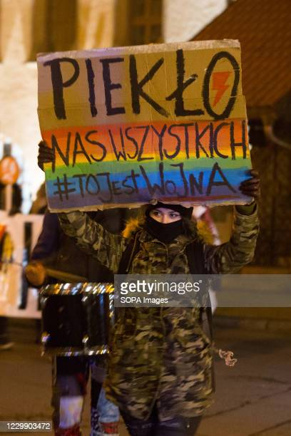 Woman holds a placard with an inscription 'Hell of us all #ThisIsWar' during the Women's Strike. 'You will never walk alone', under this slogan,...