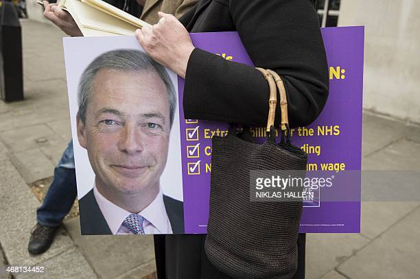 A woman holds a placard with party's key election pledges after Nigel Farage's photocall in central London on March 30 2015 AFP PHOTO / NIKLAS HALLE'N