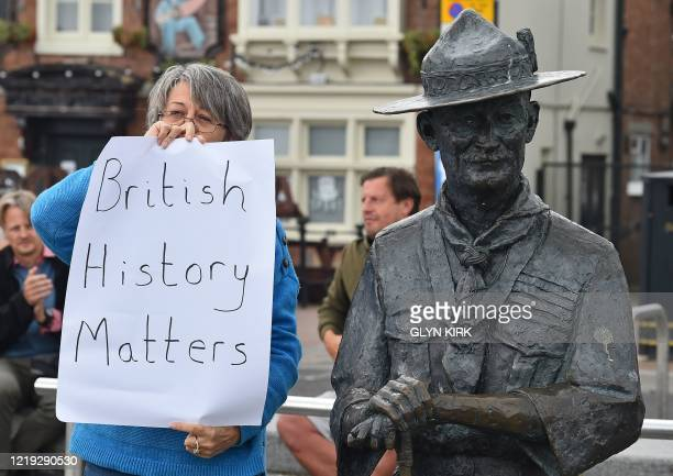 """Woman holds a placards reading """"British History Matters"""" alongside a statue of Robert Baden-Powell, the founder of the Scout movement, on the..."""