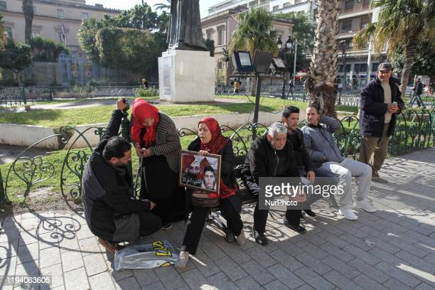 A woman holds a portrait of a young man who was killed during the 20102011 uprisings as she sits with other persons on a public bench during the...