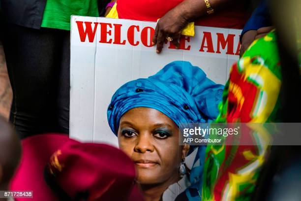 A woman holds a portrait of Grace Mugabe during a gathering of President's supporters at his party headquarters to show support to Grace Mugabe...