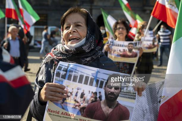 A woman holds a portrait of Iranian wrestler Navid Afkari during a demonstration on the Dam Square in Amsterdam the Netherlands on September 13...