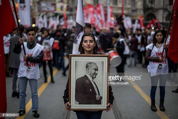 A woman holds a portrait of Mustafa Kemal Ataturk during a rally marking the 93rd Anniversary of Turkey's Republic day on October 29 2016 in Istanbul...