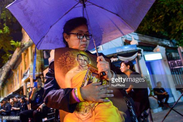 A woman holds a portrait of Thailand's late King at Grand Palace in Bangkok Thailand 05 October 2017