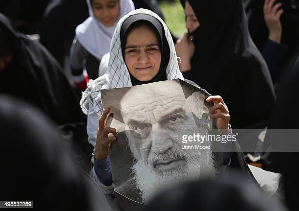 A woman holds a portrait of the Ayatollah Khomeini outside Khomeini's shrine on the 25th anniversary of his death on June 4 2014 on the outskirts of...