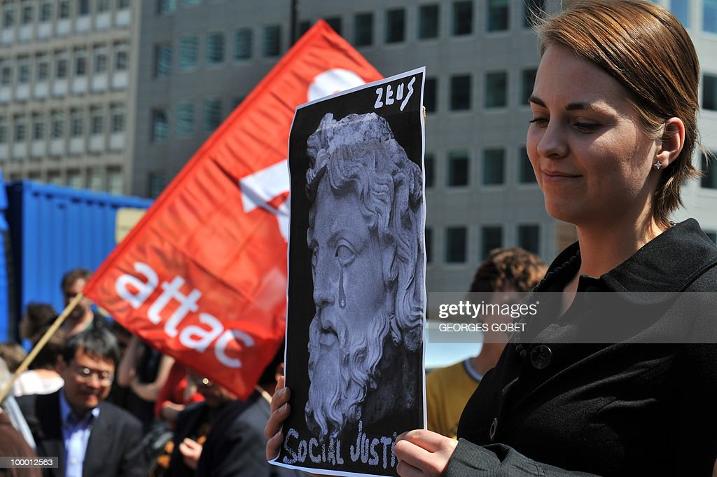A woman holds a portrait of Zeus 'crying' and reading 'Social Justice' during a demonstration in solidarity with the Greek workers in front of the EU Commission bulding on May 20, 2010 in Brussels. Meanwhile, more than 20,000 Greeks took to the streets of Athens and second city Thessaloniki on Thursday in a new general strike against the government's debt-dictated austerity spending cuts and pension reform.