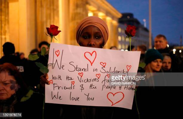 TOPSHOT A woman holds a poster and flowers to show her solidarity with the victims and their families of the Hanau killings as she attends a vigil in...