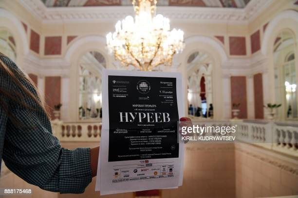 A woman holds a poster announcing the 'Nureyev' ballet premiere at the Bolshoi theatre hall on December 8 2017 in Moscow The Bolshoi will premiere...