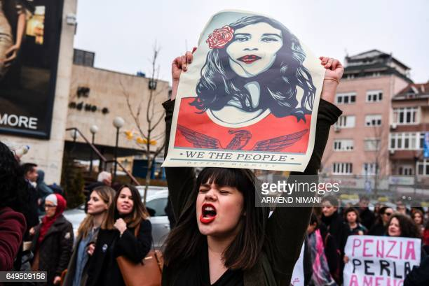 TOPSHOT A woman holds a poster by US artist Shepard Ferey and reading 'We the people defend dignity' as Kosovo feminist supporters take part in a...