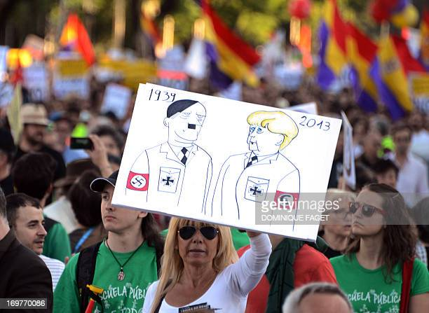 A woman holds a poster comparing German Chancellor Angela Merkel to Nazi dictator Adolf Hitler during a demonstration against the troikaof...