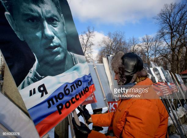 A woman holds a poster during an opposition march in memory of murdered Kremlin critic Boris Nemtsov in central Moscow on February 25 2018 The...