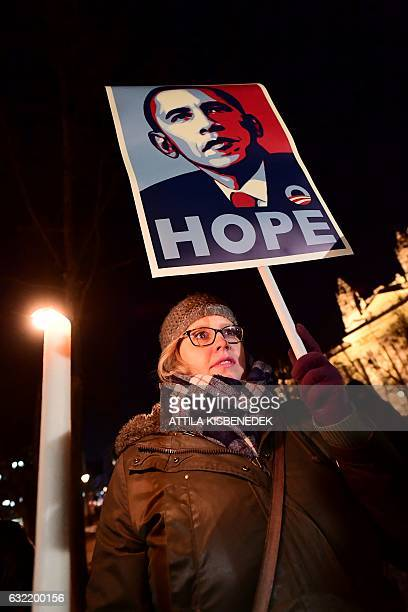 A woman holds a poster featuring outgoing US president Barack Obama during an anti Donald Trump protest on the day of his inauguration as US...