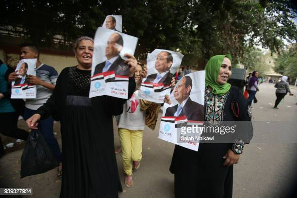 A woman holds a poster of Egyptian President Abdel Fattah alSisi on the last day of the 3day presidential elections on March 28 2018 in Cairo Egypt...