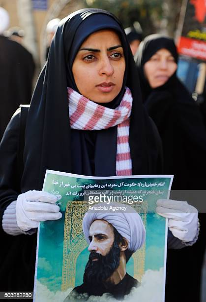 A woman holds a poster of Nimr Baqir alNimr during a protest rally outside the embassy of Saudi Arabia against the execution of prominent Saudi Shia...
