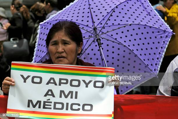 A woman holds a poster reading 'I support my doctor' during a protest against a new law that penalizes medical malpractice near the Health Ministry...