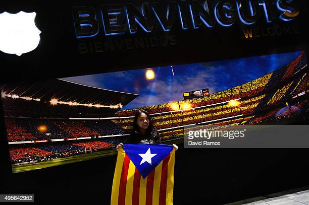 A woman holds a ProIndependence Catalan flag as she poses for a picture in front of a picture of the Camp Nou stadium ahead of the UEFA Champions...