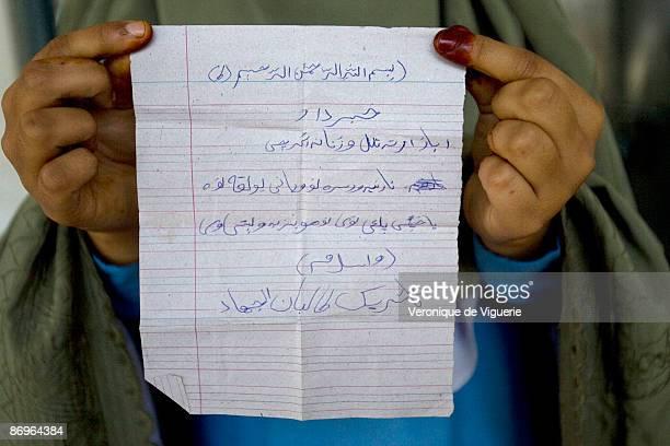 A woman holds a propaganda leaflet that was distributed by Taliban militants in Mardan bazaar April 1 2009 in Mardan Swat Valley Pakistan It lists...