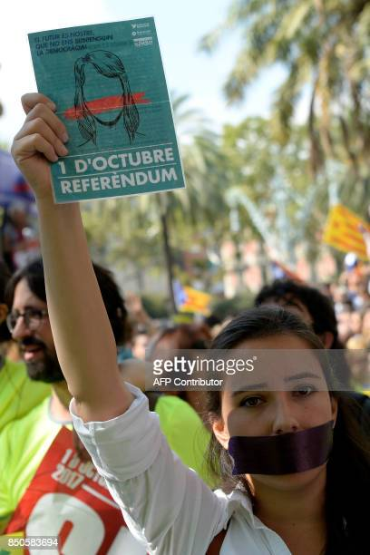 A woman holds a proreferendum flyier outside the high court in Barcelona on September 21 2017 After a daylong protest that lasted well into the night...