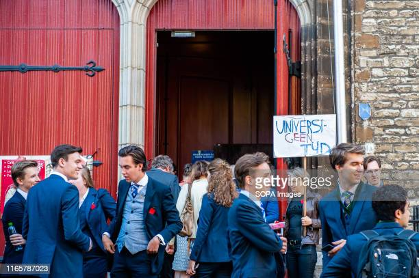 Woman holds a protest placard while University students go in, for the official ceremony. As the Executive Board of Leiden University attended the...