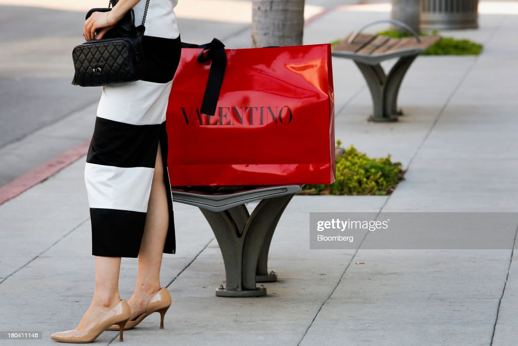 A woman holds a purse while standing next to Valentino Fashion Group SpA shopping bag on Rodeo Drive in Beverly Hills, California, U.S., on Wednesday, Sept. 11, 2013. The U.S. Census Bureau is scheduled to release retail sales figures on Sept. 13. Photographer: Patrick T. Fallon/Bloomberg via Getty Images