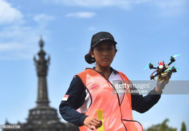 A woman holds a race drone during the FAI Drone Racing World Cup event in Denpasar on Indonesia's resort island of Bali on April 7 2018 / AFP PHOTO /...