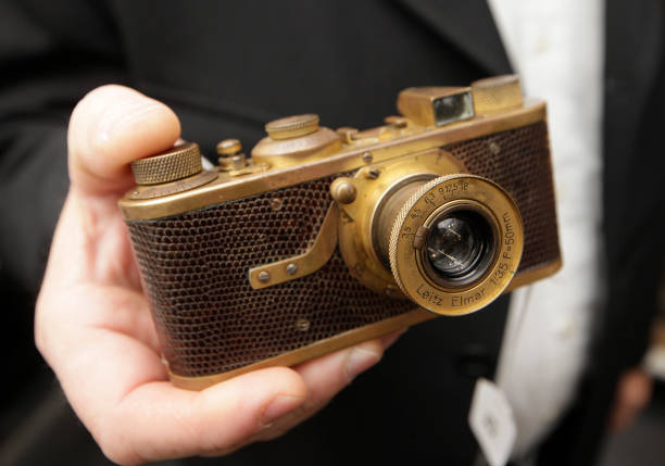 a woman holds a rare leica i a luxus gold plated camera dated 1929
