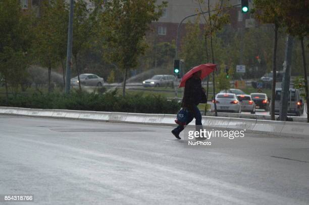A woman holds a red umbrella as she walks across a raindrenched road during a rainy autumn day in Ankara Turkey on September 26 2017 The temperature...