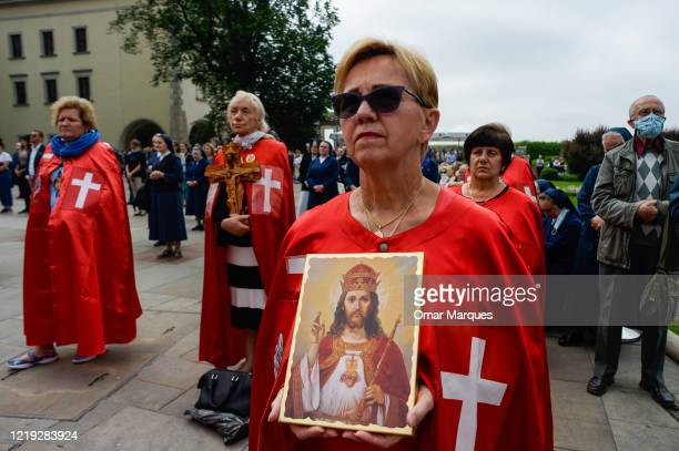 A woman holds a religious portrait as she takes part in a collective mass on  Krakow's UNESCO listed Wawel Castle during the Catholic holiday Corpus...