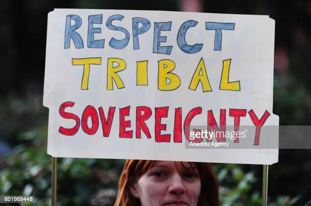 A woman holds a 'Respect Tribal Sovereignty' sign during a protest showing solidarity with the 'Native Nations Rise' march on Washington DC against...