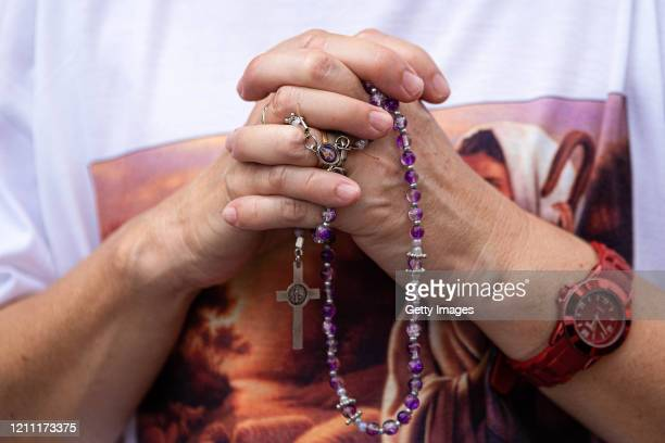 A woman holds a rosary while she prays during a mass called by the Argentine Catholic Church in rejection of a bill proposed by President Alberto...