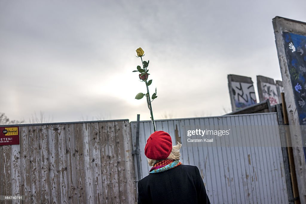 A woman holds a rose after a section of the Berlin Wall was removed to make way for a luxury apartments development on March 27, 2013 in Berlin, Germany. Activists were seeking to stop a stretch of the Berlin Wall, known as the East Side Gallery, from being developed on by a real estate development company. A previous attempt by the developer to remove approximately 25 meters of the wall sparked protests that led to minor clashes with police. Negotiations had been underway and city officials had even offered the developer an alternative property, though removal continued today unannounced and to the surprise of opponents. The East Side Gallery is over one kilometer long and is among the city's biggest tourist attractions.