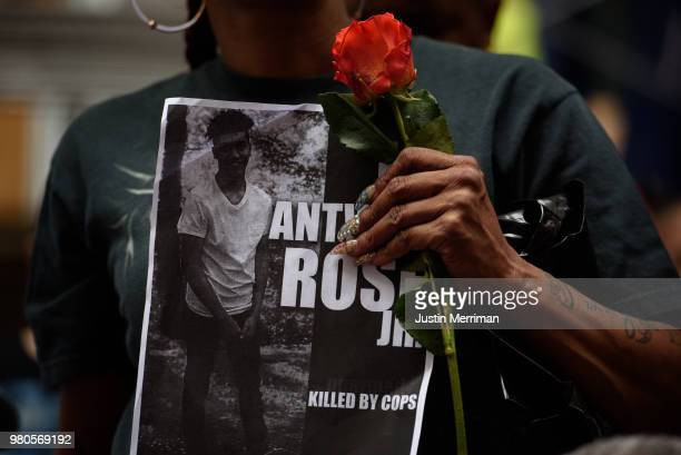 A woman holds a rose and a sign for Antwon Rose as she joins more than 200 people gathered for a rally to protest the fatal shooting of Rose at the...
