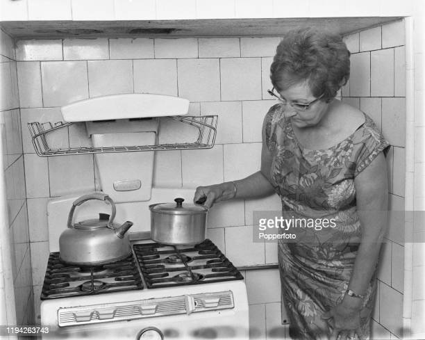 Woman holds a saucepan over the ring of a gas cooker in her kitchen in England in September 1967. Domestic gas cookers in the United Kingdom are...