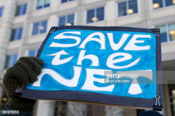 TOPSHOT A woman holds a 'Save the Net' protest sign during a demonstration against the proposed repeal of net neutrality outside the Federal...