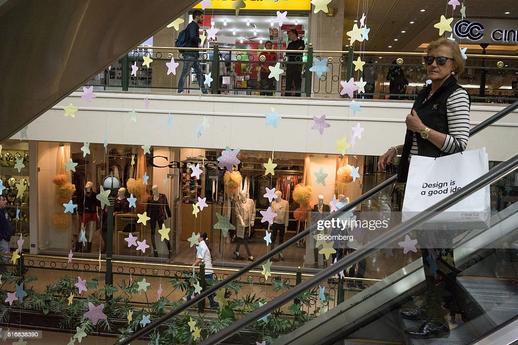 A woman holds a shopping bag as she rides the escalator at the Centro Commercial Andino mall in Bogota, Colombia, on Wednesday, March 16, 2016. Colombia's central bank raised its benchmark interest rate for a seventh straight month as the inflation outlook continued to worsen and economic growth unexpectedly accelerated. Mariana Greif Etchebehere