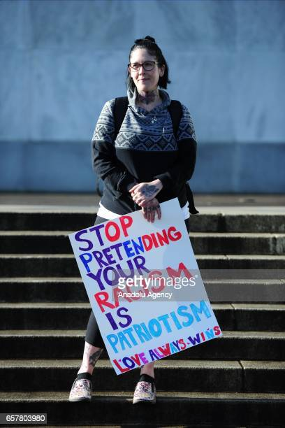 A woman holds a sign against racism on the steps of the State Capitol in a show of love against a planned proTrump Make America Great Again rally in...