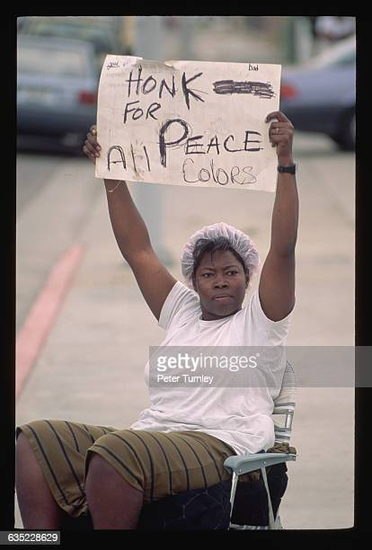 Woman holds a sign asking motorists of all races to honk their horns for peace during the riots which ensued after white Los Angeles police officers...
